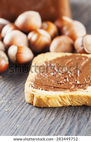 Chocolate over rusk, with hazelnuts and jar on the background, focus on first part of rusk, vertical image - stock photo