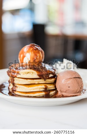 Chocolate pancakes with ice cream on top - soft focus point - stock photo