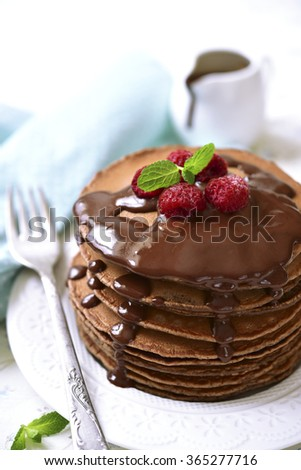 Chocolate pancakes with raspberry and chocolate sauce on a white background. - stock photo