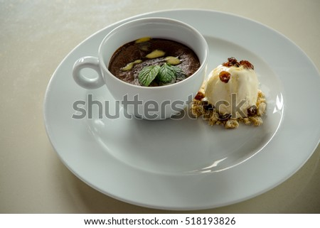 Chocolate parfait with mint leaves and ice cream on the side