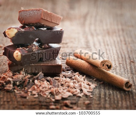 Chocolate pieces  with cinnamon stick on wooden background