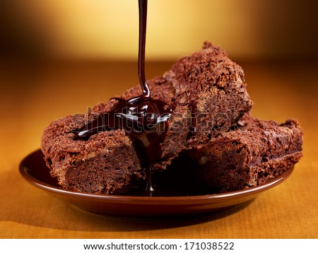 chocolate pouring over slices of chocolate cake - stock photo