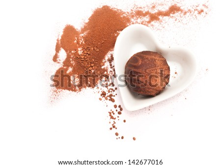 Chocolate praline in a heart-shaped plate on white background - stock photo