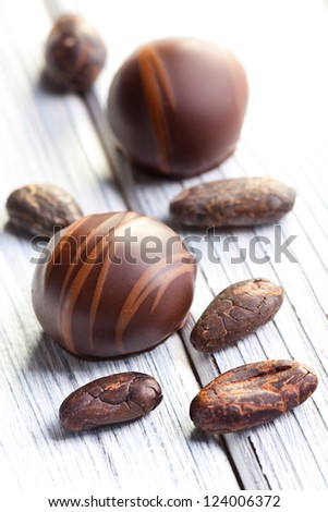 chocolate pralines and cocoa beans on white table