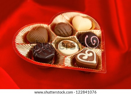 chocolate pralines in golden heart shape box on red silk background. selective focus - stock photo