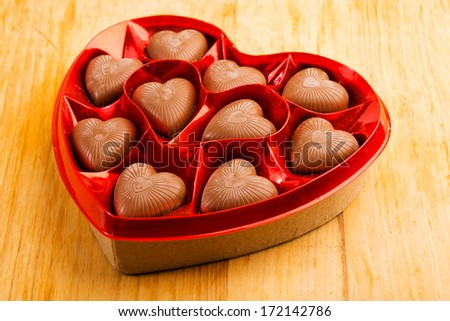 chocolate pralines in red heart shape box on table - stock photo
