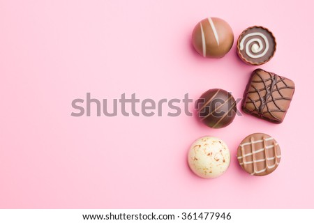 chocolate pralines on pink background - stock photo