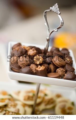 Chocolate pralines on white plate, very shallow focus - stock photo