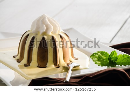 chocolate pudding with vanilla sauce and mint on white plate