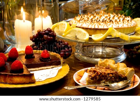 Chocolate Raspberry Torte, Lemon Meringue Pie, and Pecan Pie all surrounded by warm candlelit Kitchen. - stock photo