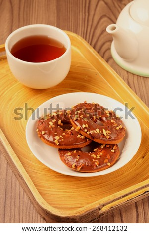 Chocolate ring cookies on a plate on wooden background - stock photo