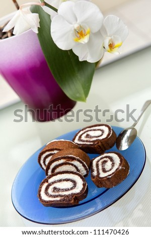 Chocolate roulade with orchid in background - stock photo
