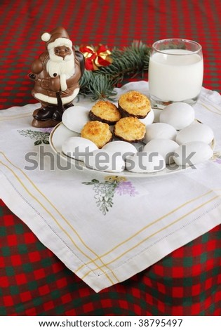 Chocolate Santa Claus with coconut and ginger cookies and glass of milk at background - stock photo