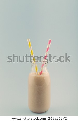 Chocolate Smoothie in a Retro Milk Bottle with Striped Drinking Straws on a Blue Background with Retro Effect.  - stock photo
