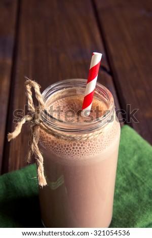 Chocolate smoothie (milkshake) with straw in jar on dark wooden table - stock photo