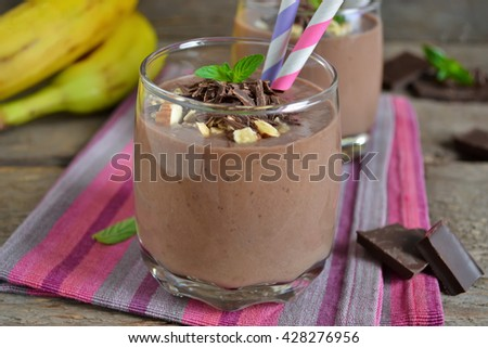 chocolate smoothie with banana and almonds on a wooden background - stock photo