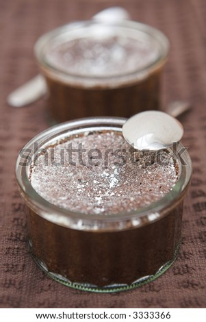 Chocolate souffle desserts lightly dusted with icing sugar - shallow dof - stock photo