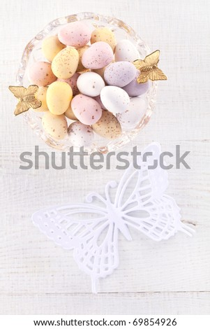 chocolate speckled eggs in bowl with paper batterfly on white table, shallow dof