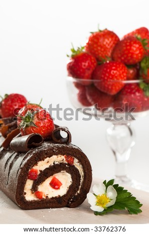 Chocolate & strawberry swiss roll with bowl of strawberries in background - stock photo