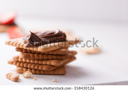 Chocolate sweet melting nougat cream on cookies on a white plate with copy space, horizontal, closeup, selective focus