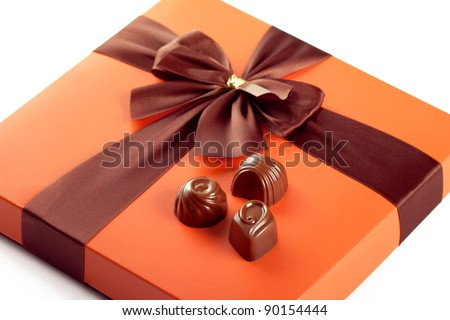 Chocolate sweets and beautiful gift box with ribbon bow, closeup shot - stock photo
