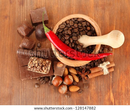 Chocolate sweets, mortar with coffee beans on wooden background - stock photo