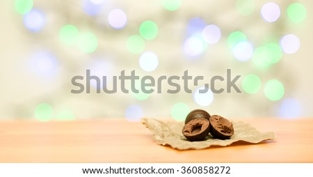 Chocolate sweets on wooden and color lights background - stock photo