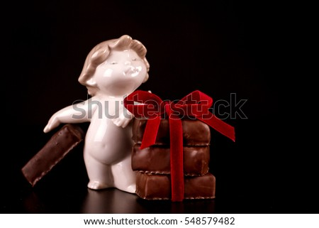 Chocolate sweets with red ribbon and porcelain angel on dark background for Valentine's day