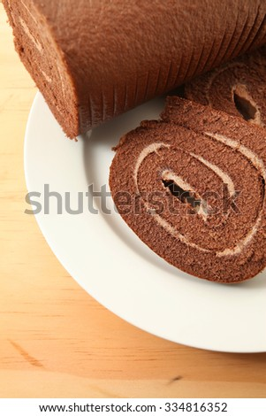 chocolate Swiss roll cake on wooden table background