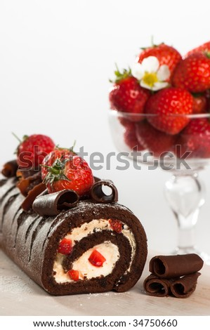 Chocolate swiss roll decorated with strawberries - stock photo