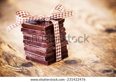 Chocolate tape connected to the wooden table. - stock photo