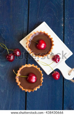 Chocolate tarts with cherry. Homemade mini cherry tart with chocolate ganache on gray background. Place for text, copy space - stock photo
