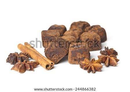 Chocolate truffles and cinnamon on white background - stock photo