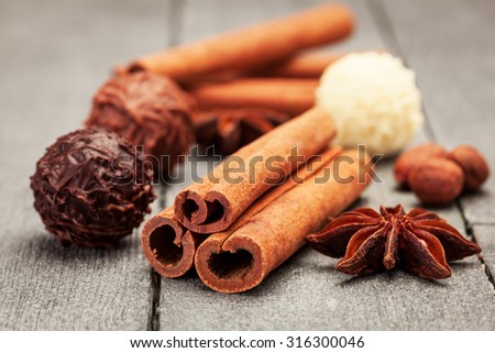 Chocolate truffles and spices over wooden table - stock photo