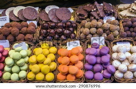 Chocolate, truffles, candies, cherry in chocolate and colorful macaroons on market stall - stock photo