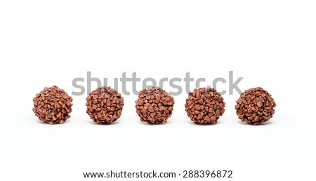 Chocolate truffles in a row, isolated on white - stock photo