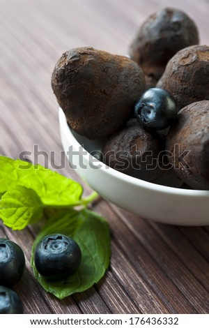 Chocolate truffles in white porcelain bowl with blueberry and leaf of mint on wooden background