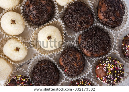 chocolate truffles selection white and with hundreds and thousands shot from above on white wooden boards landscape - stock photo