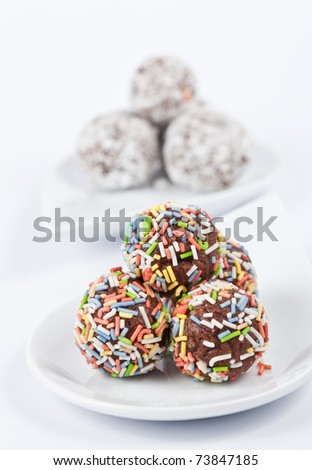 Chocolate truffles with colorful toppings on white - stock photo