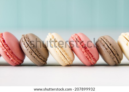 Chocolate, vanilla and strawberry macaroons (aka macarons) on a white wooden table with a robin egg blue background. Vintage Style. - stock photo