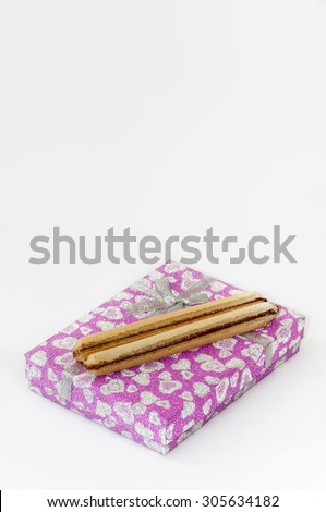 Chocolate wafers on the pink gift box with bow.