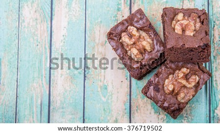 Chocolate walnut brownies over wooden background - stock photo
