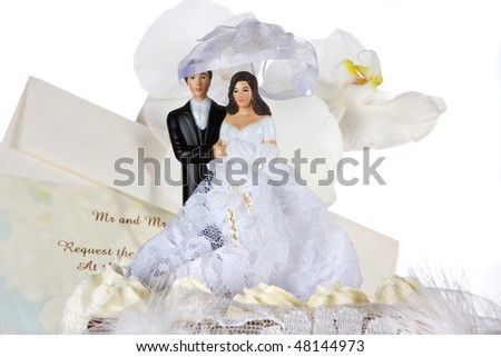 Chocolate wedding cake with cake topper, invitation card and orchids - stock photo