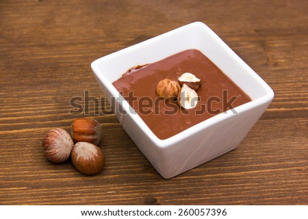 Chocolate with hazelnuts on bowl on wooden table - stock photo