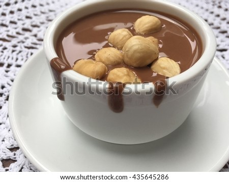 Chocolate with hazelnuts on the lace. White cup for your text. Milk chocolate. Liquid milk chocolate.  - stock photo