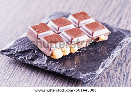 Chocolate with hazelnuts over black stone, horizontal image