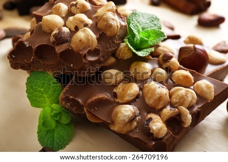 Chocolate with nuts, spices and mint on paper, closeup - stock photo