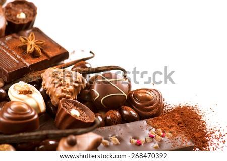 Chocolates border isolated on white background. Chocolate. Assortment of fine chocolates in white, dark, and milk chocolate. Variety of Praline Chocolate sweets - stock photo