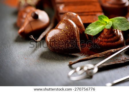 Chocolates. Chocolate sweets. Heart shaped praline. Assortment of fine chocolates in dark and milk chocolate with vanilla and mint. Praline  - stock photo