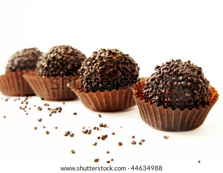 Chocolates in a chocolate shaving on a white background
